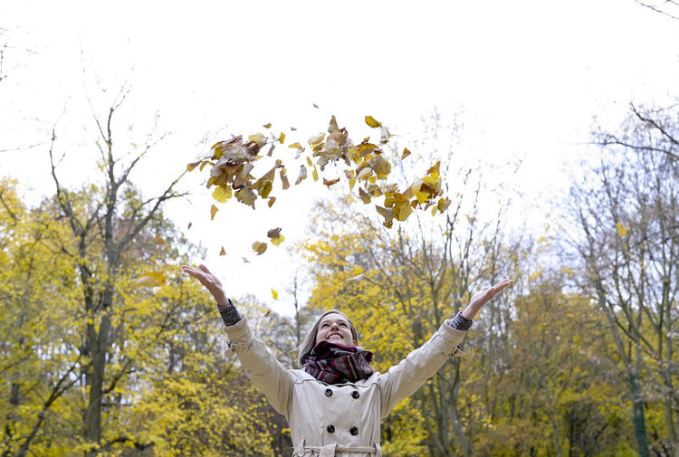 young woman throwing autumn leaves Autumn Confidence  Fun Happy Laughing Tossing Woman Attractive Beautiful Woman Cheerful Enthusiasm Foliage Girl Leaves Lifestyles Millennials Park Playful Pleasure Relaxation Sheets Smiling Teenager Throwing  Young Women