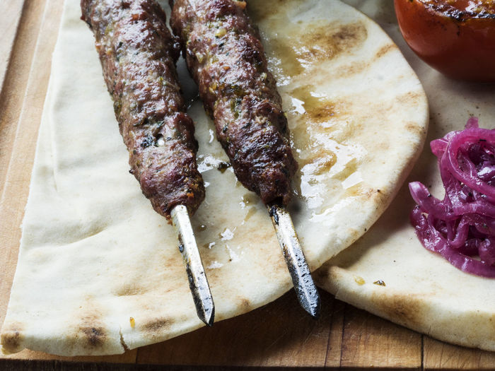 Close-up of fresh shish kebab lamb meat on skewers over cutting board