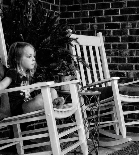Side view of girl sitting on chair at patio