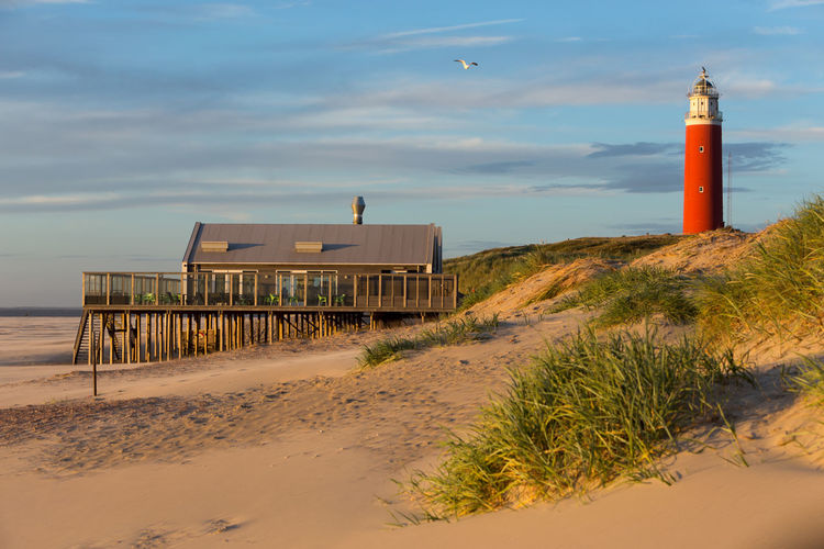 Architecture Beach Building Exterior Built Structure Calm Coastline Day Direction Grass Guidance Leading Lifeguard Hut Lighthouse Lighthouse Outdoors Protection Sand Sea Shore Sky Solitude Tower Tranquil Scene Tranquility Water