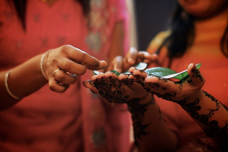 Midsection Of Woman Performing Henna Tattoo Rituals