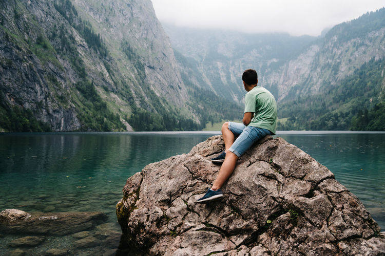 Young man sitting on rock looking at the lake Königssee Obersee Adult Adults Only Adventure Beauty In Nature Casual Clothing Day Full Length Lake Lake View Lakeshore Leisure Activity Lifestyles Men Mountain Mountain Range Mountains Nature One Person Outdoors People Real People Rock - Object Scenics Sitting Sky Tree Vacations Water Wilderness Young Adult