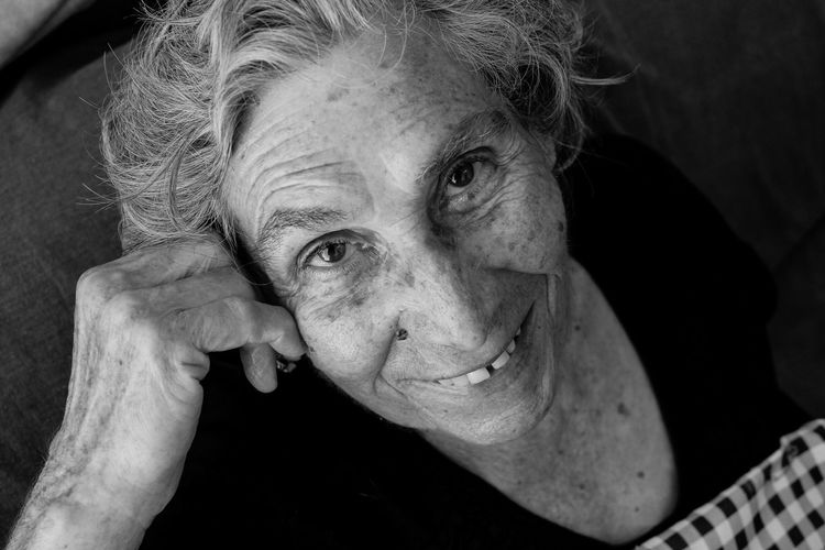 Casual Clothing Close-up Domestic Life Grandmother Gray Hair Headshot Home Interior Human Body Part Human Face Indoors  Leisure Activity Lifestyles Looking At Camera One Person One Senior Woman Only Portrait Real People Retirement Senior Adult Senior Women Sitting Smiling Women Wrinkled
