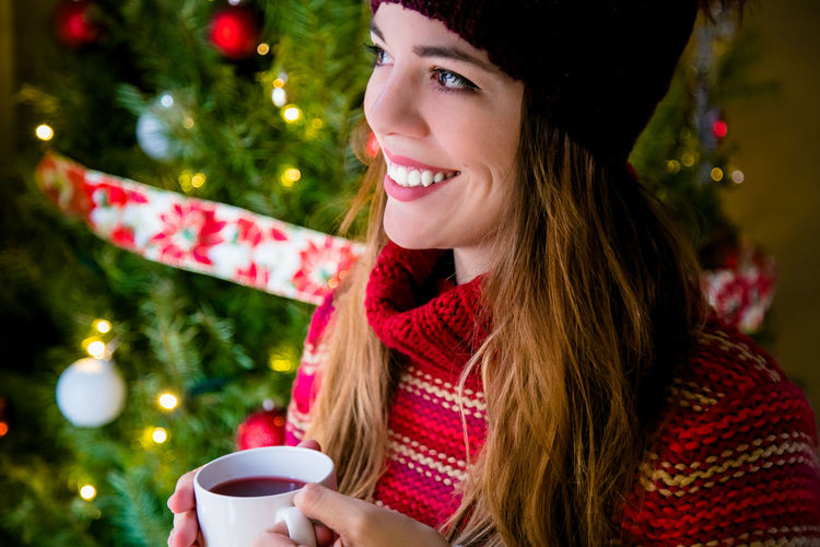 Young woman drinking coffee cup on christmas tree