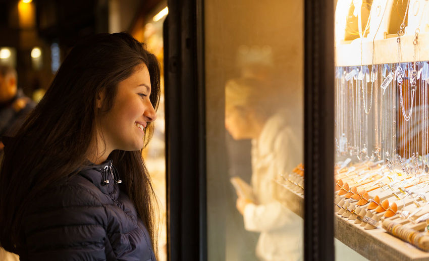 Side view of smiling woman looking towards jewelry in shop