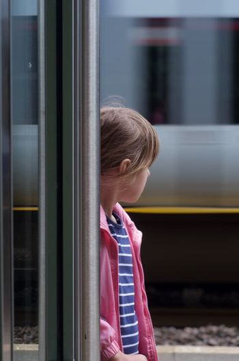 Rear view of girl looking at a train window