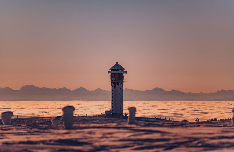 Lighthouse on beach by sea against sky during sunset