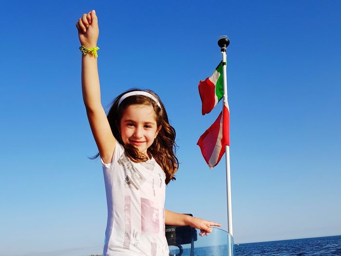 Children Only Child Arms Raised Portrait Blue One Person Childhood Human Body Part One Girl Only Human Arm Looking At Camera Girls Sky Outdoors Summer Smiling People Sea Clear Sky Flag Italian Happy