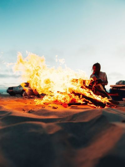 Summer is here. Burning Heat - Temperature One Person Fire Real People Fire - Natural Phenomenon Sky Leisure Activity Flame Nature Men Sitting Lifestyles Adult Land Orange Color Bonfire Outdoors Beach Campfire