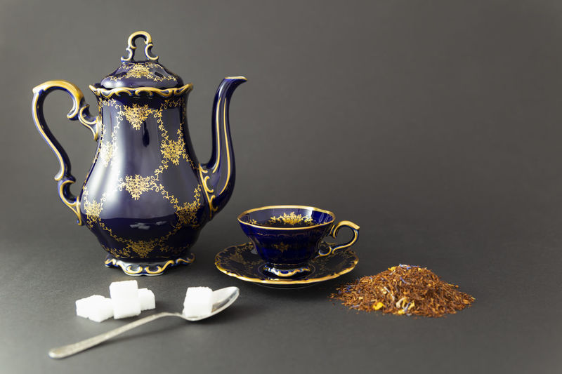 Close-up of tea cup on table against black background