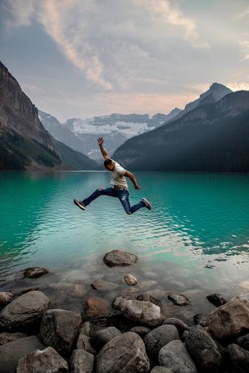Full length of man jumping on rocks by lake against mountains