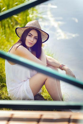 Portrait of woman wearing hat sitting outdoors