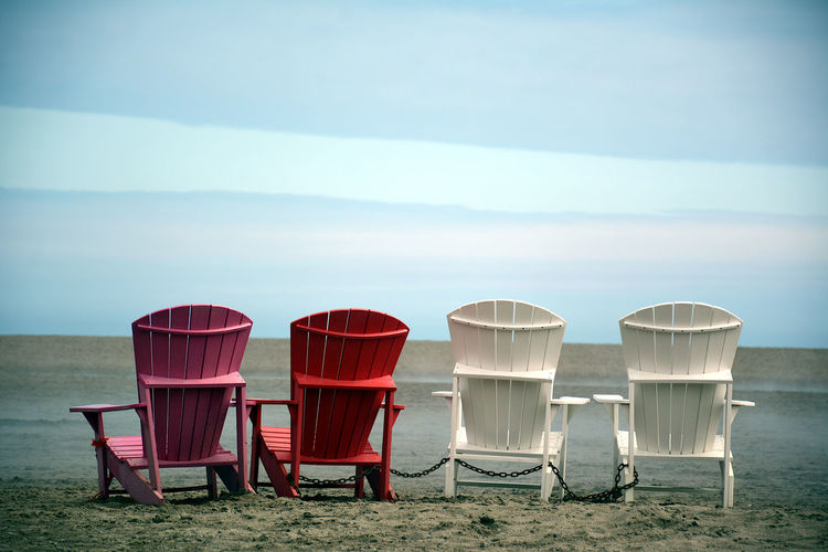 Empty chairs on beach against sky