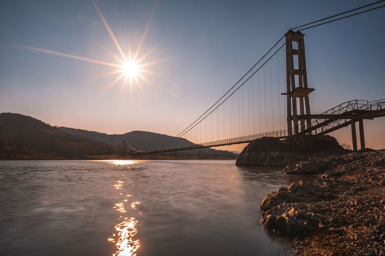 The longest suspension bridge in Bulgaria over Studen Kladenez dam with distance between the two towers of 260m. The only way to reach Lisicite village Reflection Water Sunset Nature Sky Bridge Travel Tower Lake Mountain Direction Pylon Way Suspension Dam Bulgaria Metal Overcast Wooden Suspension Bridge Longest Warm Clothing Connection Built Structure Bridge - Man Made Structure Sun Architecture Engineering Transportation Sunlight Beauty In Nature Sunbeam Bay Of Water Lens Flare Outdoors Bay