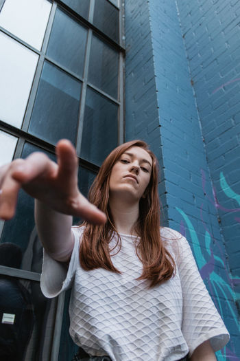 Low angle portrait of young woman standing against wall