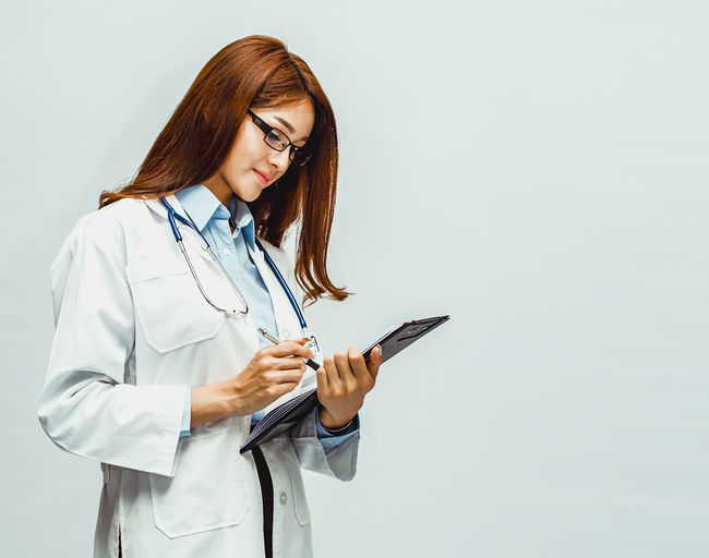A beautiful doctor is writing a record of the patient's examination results. (Concept of medical personnel) Wireless Technology Healthcare And Medicine Doctor  Communication Technology Connection Beautiful Woman Lab Coat Doctor  Doctor Office Doctor Assistant Writing Results Medical Equipment Medical Supplies Medical Instrument Medical Cannabis