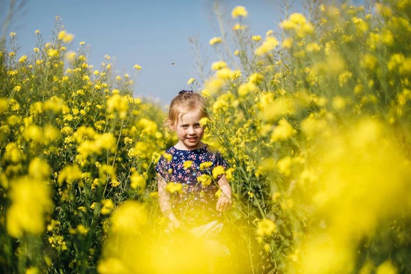 Portrait of girl amidst yellow flowers at oilseed rape field