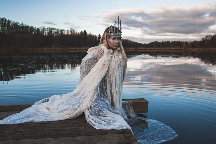 Thoughtful Woman Wearing Crown And White Costume Sitting On Pier By Lake During Sunset
