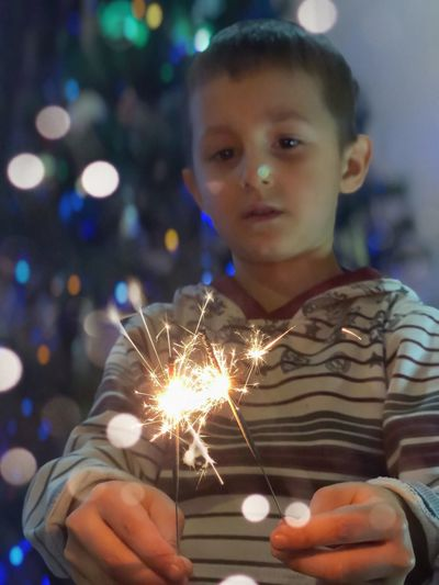 Close-Up Portrait Of Boy Holding Burning Sparkler At Night
