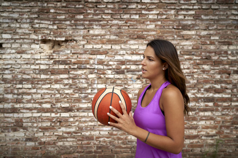 Woman holding ball while standing against brick wall