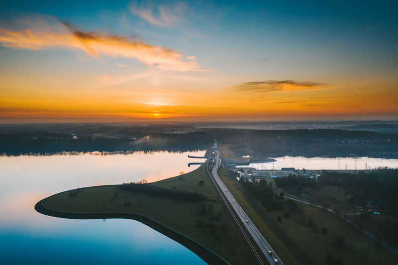 Scenic view of landscape and dam against sky during sunset