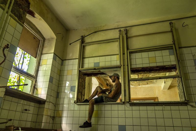 Full length of hipster sitting on window frame in abandoned building