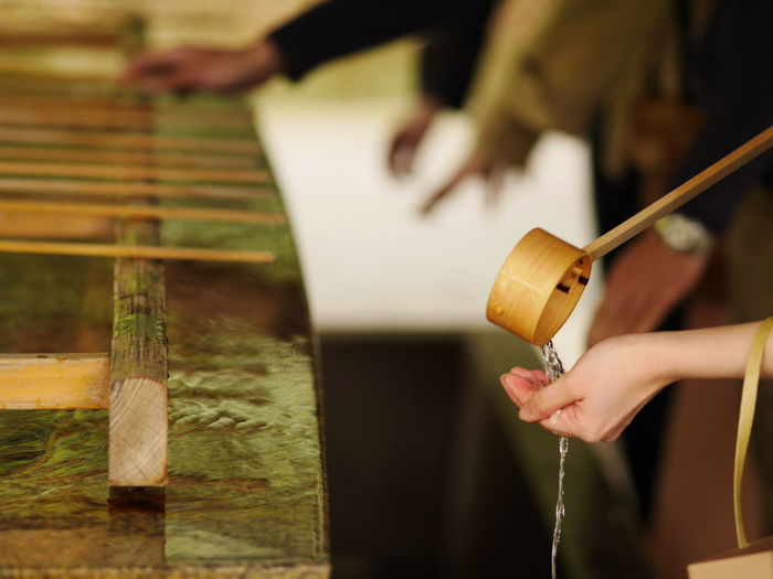 Cropped Image Of Woman Washing Hands With Bamboo Ladle