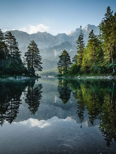 Reflection Of Trees In Lake Against Mountains And Sky
