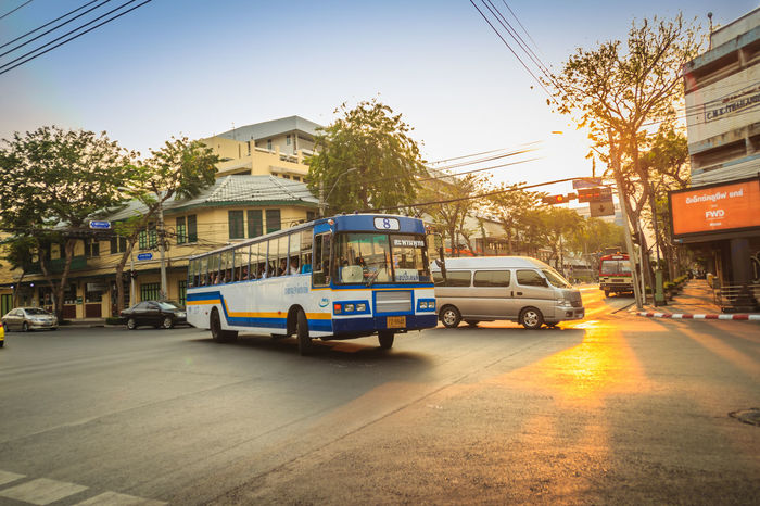Bangkok, Thailand - March 2, 2017: Local bus and cars in traffic passes through a busy junction during sunset in Bangkok, Thailand. Junction Sunset And Clouds  Traffic Traffic Jam Traffic Signs Architecture Building Building Exterior Built Structure Car City Day Junctionsquare Land Vehicle Local Bus Mode Of Transportation Motion Motor Vehicle Nature Outdoors Plant Residential District Road Sky Street Sunset Traffic Arrow Sign Traffic Light  Traffic Lights Traffic Sign Traffic Signal Trafficjam Transportation Tree