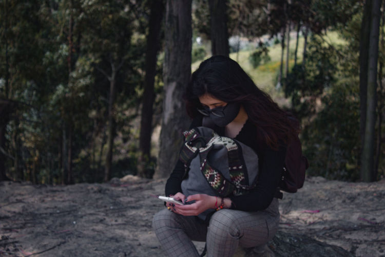 Woman using mobile phone in forest