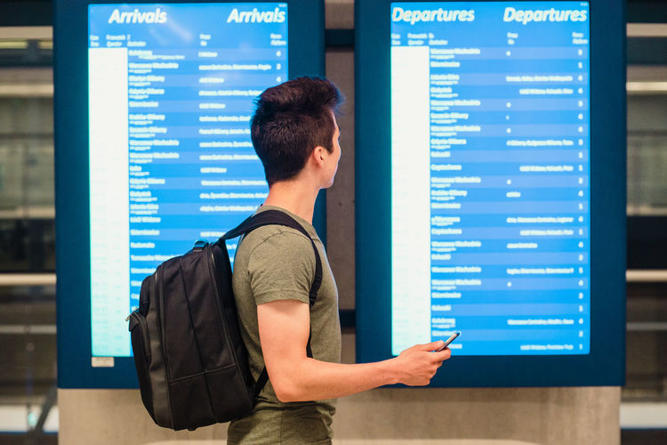 Young man using mobile phone while standing in airport