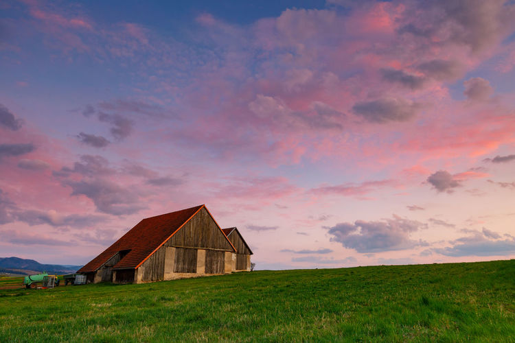House on field against sky during sunset