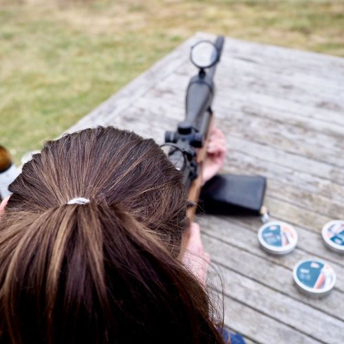 Rear view of woman holding rifle