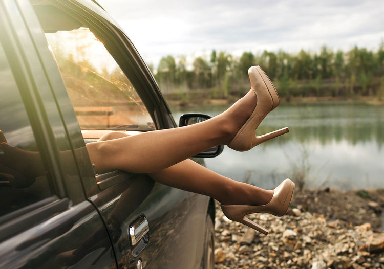 Women feet in high-heeled shoes from car window outdoors Mode Of Transportation Transportation Leisure Activity Car Real People One Person Motor Vehicle Water Lifestyles Day Land Vehicle Human Hand Nature Focus On Foreground Sky Hand Reflection Human Body Part Outdoors Finger Girl Legs Beauty In Nature High Heels Heels Woman Feet Outdoor Photography Moody Travel Window Lake Forest EyeEm Best Shots EyeEmNewHere EyeEm Selects EyeEm Gallery
