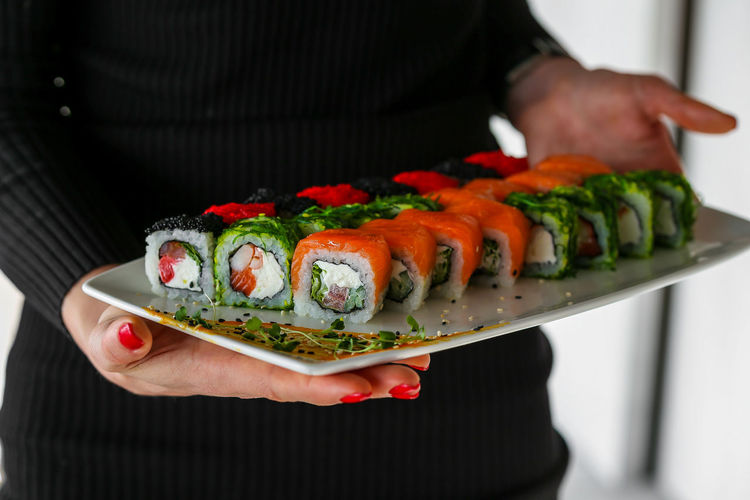 Midsection of woman holding sushi in plate