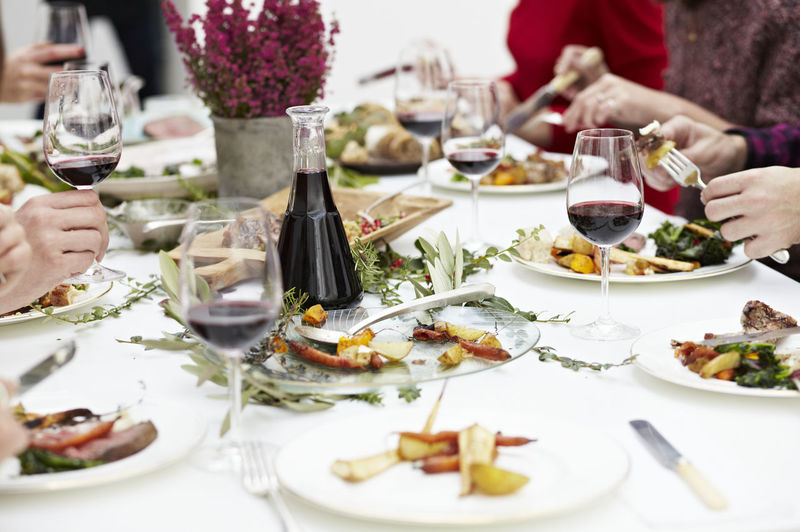 Close-up of a dinner party of friends enjoying a roast dinner with red wine. Dinner Dinner Party Food Food And Drink Indoors  Indulgence Lunch Meal Time Mealtime Meat People Red Red Wine Roasted Vegetables Table Table Setting White