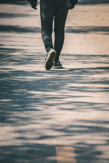 Low section of person walking on road in city