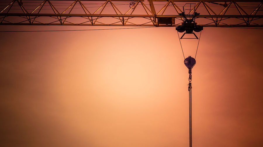 Silhouette crane against orange sky during sunset