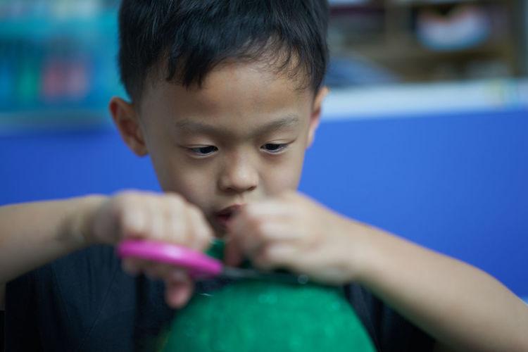 Close-up of cute boy holding scissors