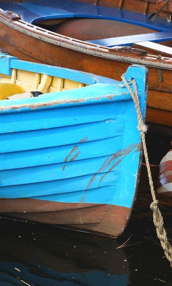 Close-up of blue ship moored on shore