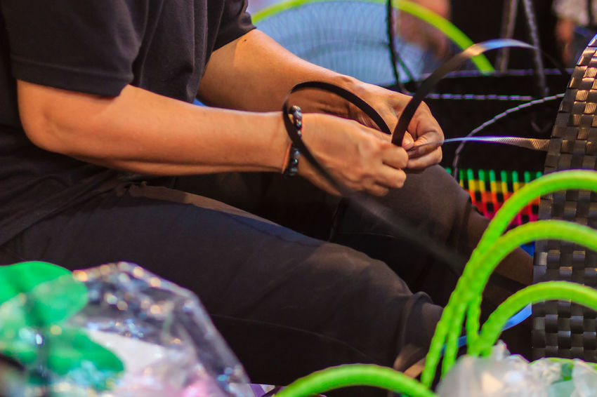 Close up hand of weaver during weaving basket made from plastic fiber. Weaver is weaving plastic basket show to the tourist in Bangkok, Thailand. Market Market Vendor Plastic Bag Weave Weaves Basket Basket Weave Close-up Day Human Hand Indoors  Marketplace Men Midsection Multi Colored People Plastic Plastic Baskets Real People Sitting Two People Weaver Weaving