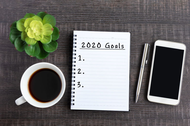 New Year Resolution Concept - 2020 Goals text on note pad with smart phone on top on desk 2020 New Year Goals Resolutions Business Coffee Concept List Target Plan Success Background White Motivation Goal Start Top View Desk Text Work Future Inspiration Strategy Office Job Change Vision Activity Chance Handwriting  NotePad Beginnings Breakfast Technology Telephone Pen Blank Wooden Wood Space Copy Note Connection Smart Phone Potted Plant Notebook Cup Table