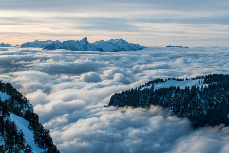 Aerial view of snow covered mountains and cloudscape against sky during winter