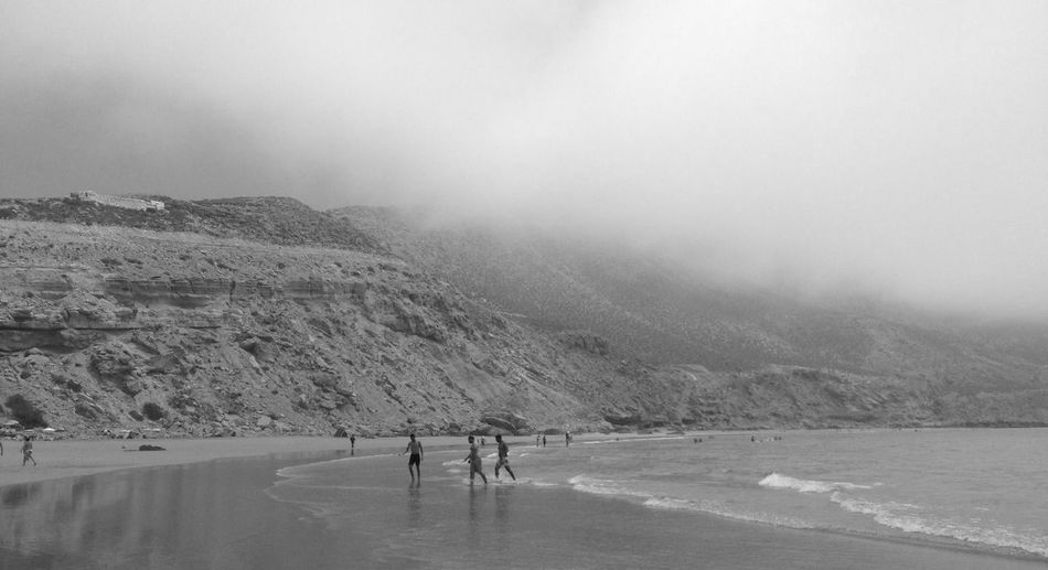Scenic View Of Beach Against Mountain During Fogy Weather