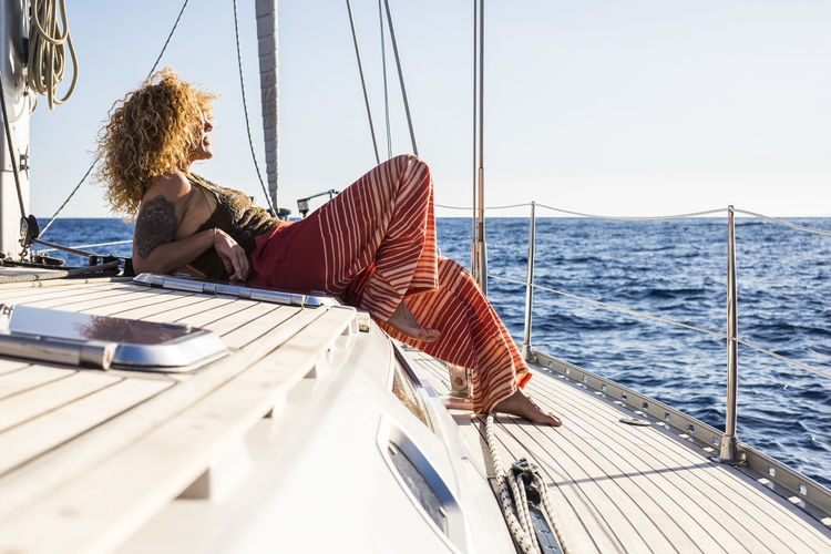 Man sitting on sailboat in sea against sky