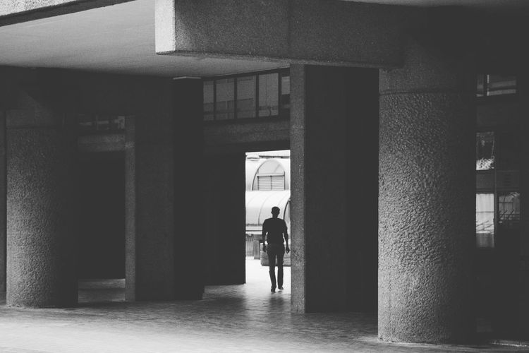 A man walks through a gap in the amazing Brutalist estate, the Barbican in London, United Kingdom. Architecture Barbican Black & White Black And White Black And White Photography Blackandwhite Blackandwhite Photography Blackandwhitephotography Building Built Structure City City Life London Modern Unrecognizable Person