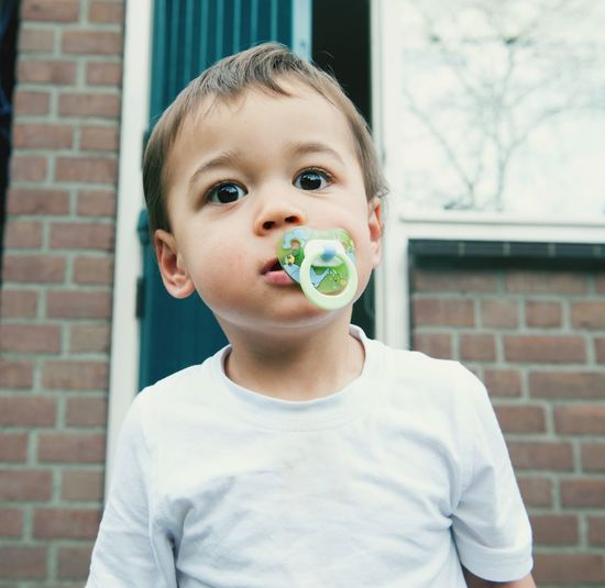 Portrait of boy with pacifier against wall