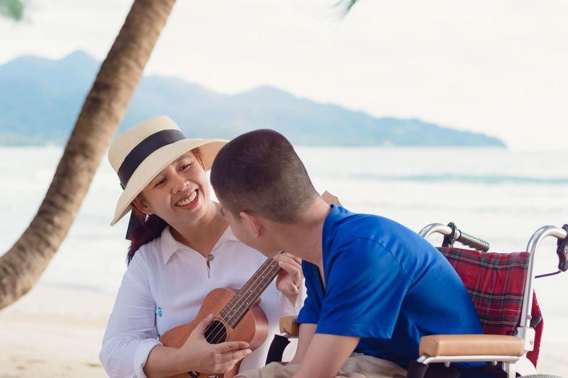 Smiling mother playing ukulele while sitting with son at beach
