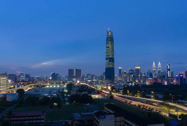 Illuminated Modern Buildings In City Against Blue Sky
