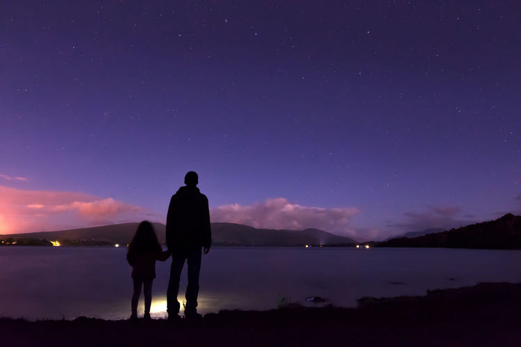 Rear view of father and daughter standing on lakeshore against sky at night